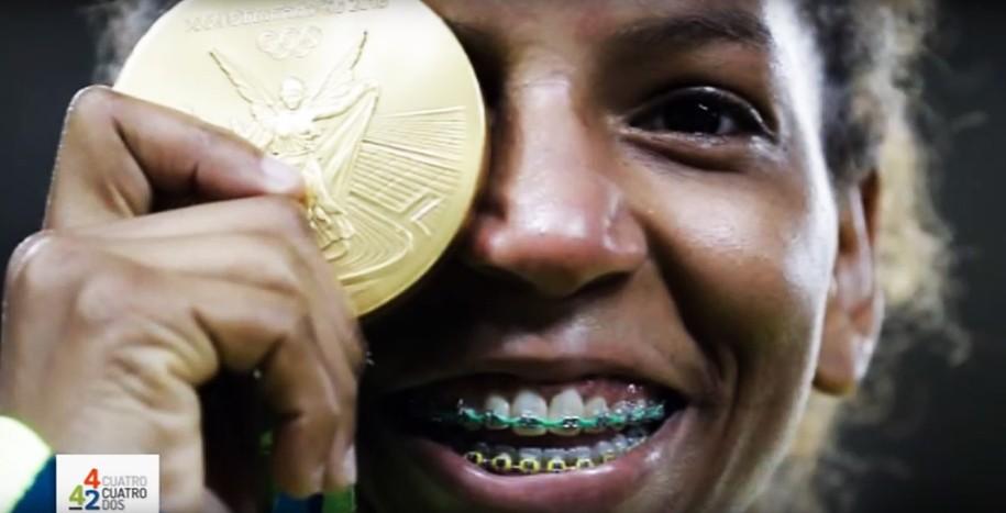 Brazilian Rafaela Silva smiles holding her Olympics gold medal in judo.